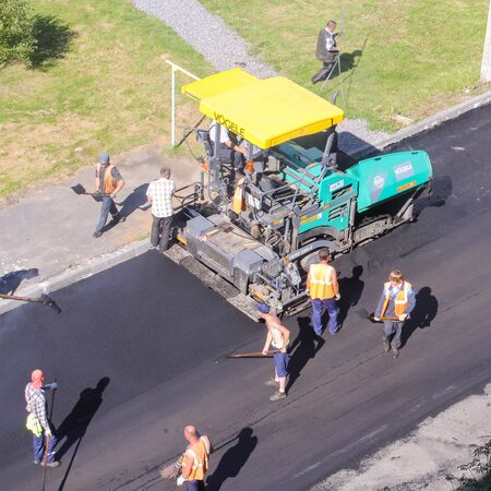 asphalting: Road workers on the job. Leningrad region, Russia - 15 June, 2015. Landscaping and asphalting of yards.