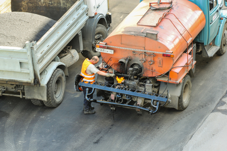 asphalting: Work at the road construction equipment. Leningrad region, Russia - 15 June, 2015. Landscaping and asphalting of yards.