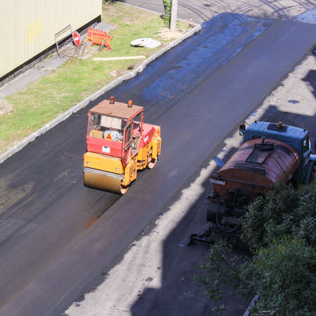 asphalting: Road construction compacted asphalt. Leningrad region, Russia - 15 June, 2015. Landscaping and asphalting of yards.