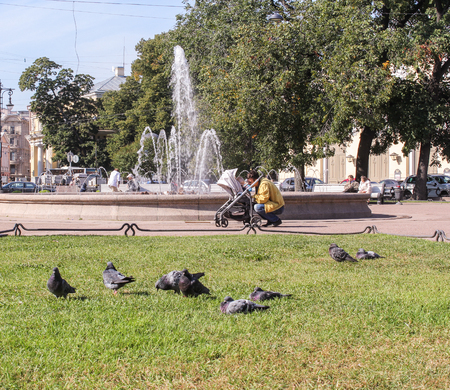 tourist spots: Young man with a child in a park with a fountain. St. Petersburg, Russia - 6 September, 2015. Excursion - tourist spots in St. Petersburg.