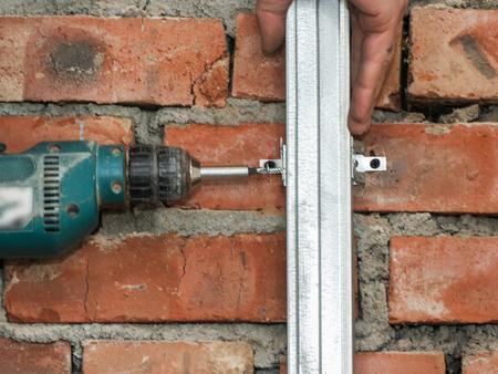 drywall: Fastening drywall racks on the wall. Stock Photo