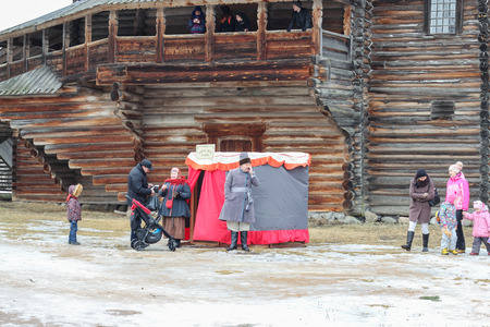 large house: People at the wall of a large house. Holiday Carnival in general Vitoslavlitsy near Novgorod. Editorial