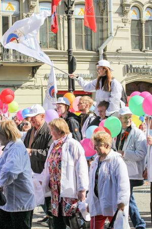 nevsky prospect: Girl with a flag on the shoulders of a young man. Day festive demonstration on the Nevsky Prospect in St. Petersburg, the first of May.