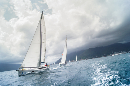 Sailboat coming one after the other with a large roll. Sea race on yachts in the Bay of Kotor Adriatic Sea.