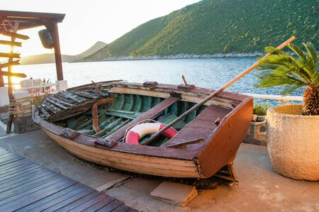 old items: Old boat in the landscape design. Vintage and retro items in the landscape design.