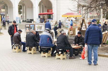 backgammon: People playing backgammon on the street. People on the streets of the city in the spring. Editorial