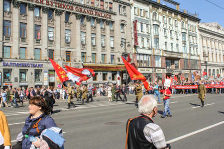 soviet flag: People in military uniform under the Soviet flag. Holiday-action Immortal regiment taking place in St. Petersburg on Nevsky Prospect.