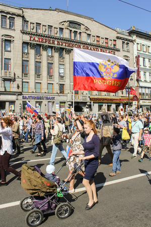 regiment: A woman with a stroller and the flag of Russia. Holiday-action Immortal regiment taking place in St. Petersburg on Nevsky Prospect. Editorial