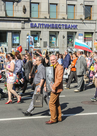 regiment: A man with a large portrait. Holiday-action Immortal regiment taking place in St. Petersburg on Nevsky Prospect.