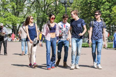 vacationers: A group of young people. Vacationers people on the lawns and gardens in the city.