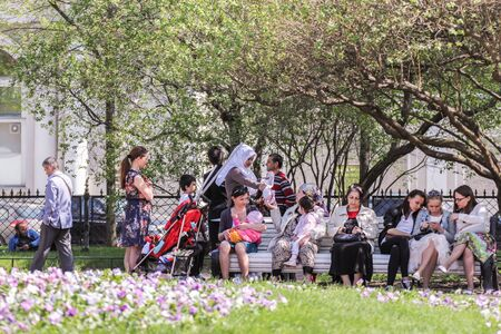 vacationers: People vacationers relax in the garden. Vacationers people on the lawns and gardens in the city.