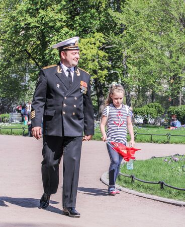 vacationers: The naval officer with a girl. Vacationers people on the lawns and gardens in the city.