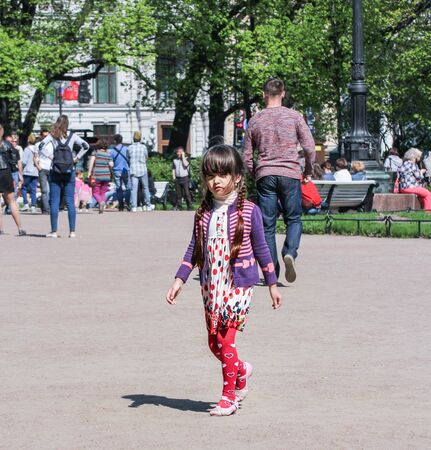 vacationers: Little girl with pigtails. Vacationers people on the lawns and gardens in the city.