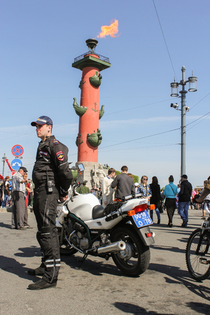 motorcycle officer: A police officer with a motorcycle. Celebration day of victory in the center of St. Petersburg.