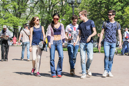 vacationers: Group of young people in the garden. Vacationers people on the lawns and gardens in the city.