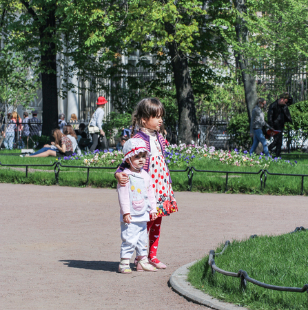 vacationers: Children in flower beds in the garden. Vacationers people on the lawns and gardens in the city. Editorial