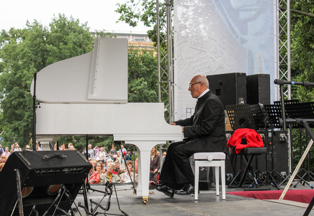 maestro: Maestro behind a white grand piano. Speech by David Goloschekin with his jazz group on the Arts Square in St. Petersburg.