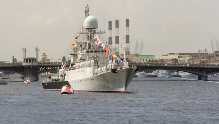 warship: Warship on board with the team. Festive parade of warships on the Neva River in St. Petersburg.