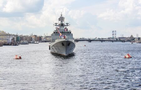 warship: A large warship in the wake of the river. Festive parade of warships on the Neva River in St. Petersburg.