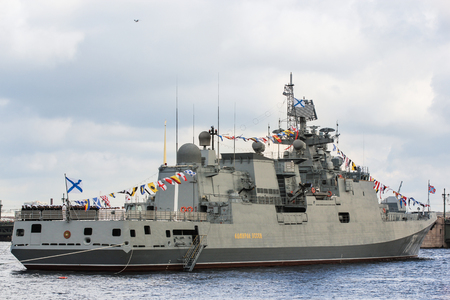Flagship military ship at anchorage. Festive parade of warships on the Neva River in St. Petersburg. Editorial