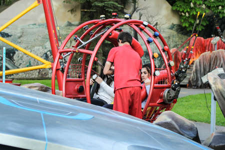 Instructor retaining girls in the capsule. Amusement and extreme rides for teenagers and adults. Editorial