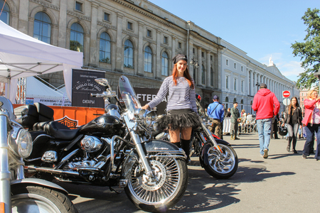 striped vest: Girl in a striped vest on motorbikes background. The annual International Festival of Motor Harley Davidson in St. Petersburg Ostrovsky Square. Editorial