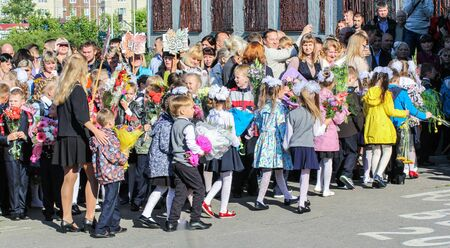 escorted: First-graders with flowers escorted to school. School holiday on the first day of autumn, the Day of Knowledge.