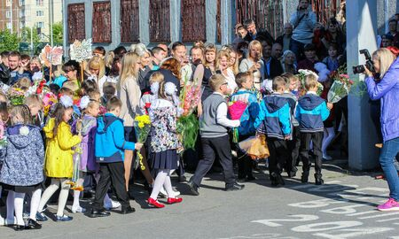 First-graders escorted to school. School holiday on the first day of autumn, the Day of Knowledge.