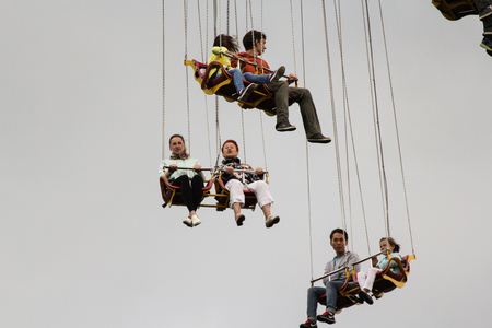 exhilaration: Hanging high in the air people. Entertainment people in a city park rides.