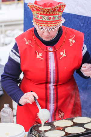 Woman Baking pancakes. People in the city at the traditional national holiday of Maslenitsa.