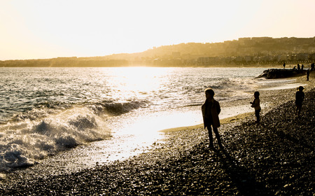 seafronts: Children by the sea at sunset. People and tourists having a rest on the Cote dAzur. Stock Photo