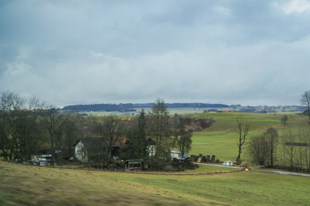 picturesque: Houses in the fields. View from the window of a train on a trip across Europe. Stock Photo