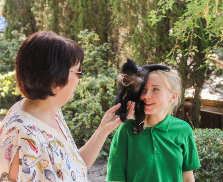 People with a monkey. Zoo and animals on the territory of the hotel Yalta Intourist.