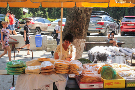 merchant: Street seller of flat cakes. Products and people in the central market of Yalta. Editorial
