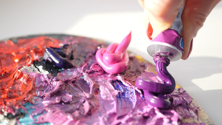 pallette: HD. artist squeezes from the tube to the palette purple oily paint.