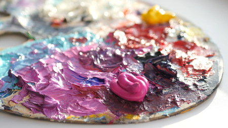 artist blends dark colors on the palette with a brush.