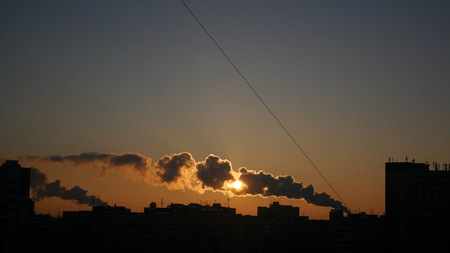 beautiful sunset on a background of cityscape with smoking chimneys.