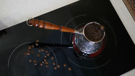 A delicious aromatic coffee is on the stove brewed. Imagens