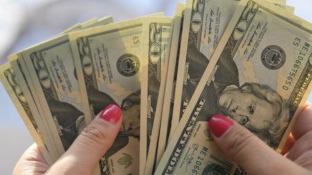 Girl looks at the new twenty-dollar bills in her hands, Imagens