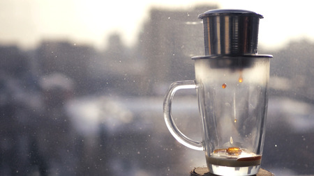 Making coffee in Asia, a drop falling into a glass bowl. Against the background of the citys spring landscape in the city. 1920x1080.