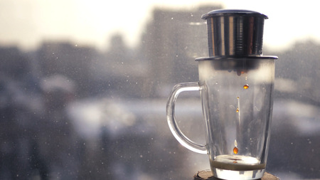 Coffee drips drops in a cup on a background of the urban landscape outside the window. Brew coffee in Vietnamese