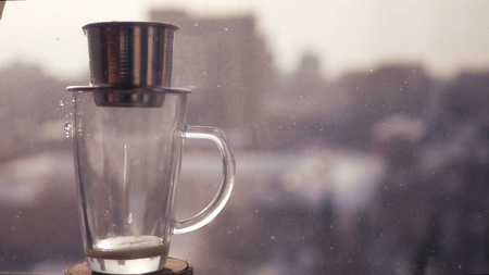 Making Fresh coffee in Asian, a drop of coffee drops in a transparent cup against the background of a blurry city landscape. HD Imagens