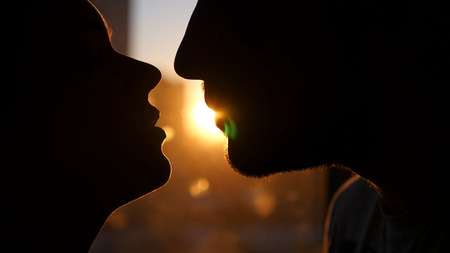 Young couple in love, look into each others eyes, against the sunset, with the effect of a lens. He runs a finger down his face.