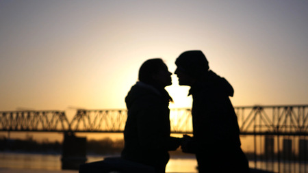 A loving couple, happy man and woman are kissing on the background of a railway bridge and sunset.