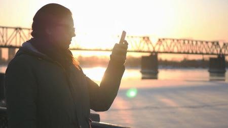 Young attractive girl is walking along the waterfront on the background of a railway bridge and a beautiful sunset, holding a phone in hands, writes a message.