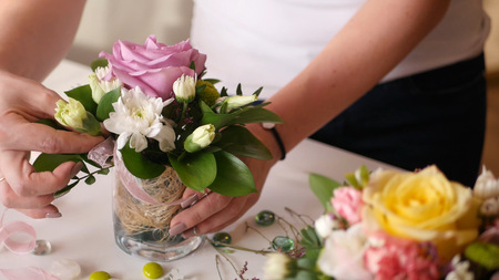 Florist girl collects a nice little bouquet of roses and other flowers in a small vase 스톡 콘텐츠