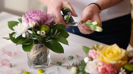 Beautiful young girl shows florist master class on making prekrassnogo bouquet of fresh flowers