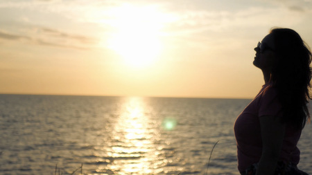 A young girl admires the beautiful sunset by the sea, a light wind blows.