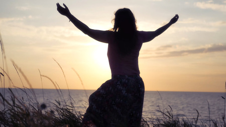 The girl rejoices the sea, the sun and the sunset, raises her hands up, whirls. . HD