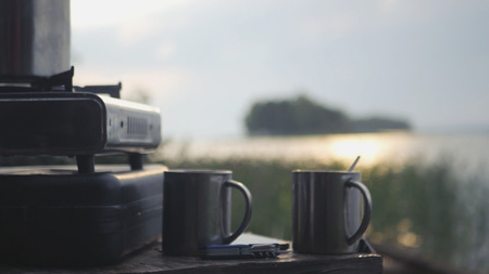 Two mugs of hot tea at a gas tourist plate against the backdrop of a lake with glare of the morning sun. With motion of the camera. HD